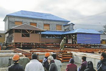 レールの上をゆっくり移動する旧明村役場庁舎.jpg